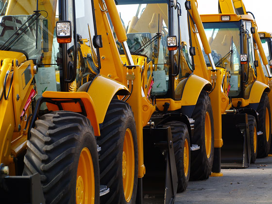 Close up of three parked pieces of heavy equipment