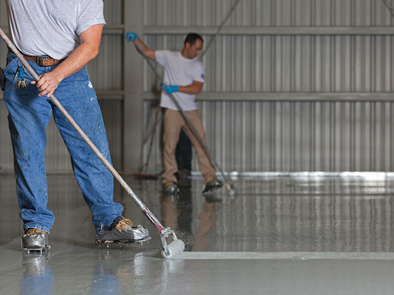 Two men rolling epoxy onto floor